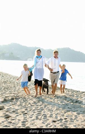 Familie zu Fuß am Strand mit Hunden - Stockfoto