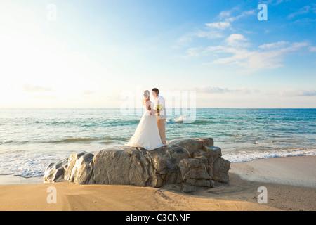 Brautpaar am Strand umarmt - Stockfoto