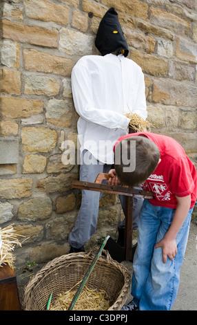 Kleiner Junge sucht in Henker Korb Wray Vogelscheuche Dorffest - Stockfoto