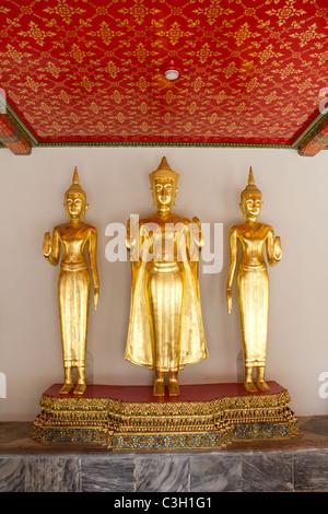 Drei Gold stehenden Buddha-Statuen an den berühmten buddhistischen Tempel Wat Pho in Bangkok, Thailand - Stockfoto