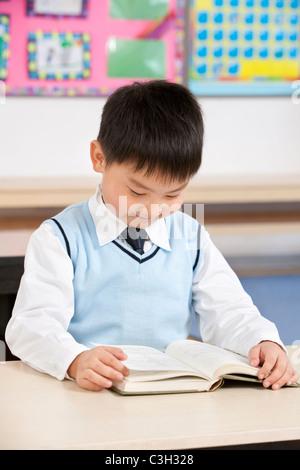 Kleiner Junge liest an seinem Schreibtisch in einem Klassenzimmer - Stockfoto