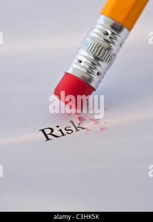 Studioaufnahme von Bleistift löschen das Wort Risiko aus Papier - Stockfoto