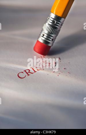 Studioaufnahme von Bleistift löschen das Wort Krise aus Papier - Stockfoto