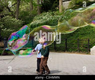 Zwei Jungen starrte ins Staunen über riesige Seifenblasen im Central Park in New York City. - Stockfoto