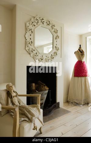 Reich verzierte Spiegel über dem Kamin im Wohnzimmer mit der Schneiderin Dummy und Mannequin Puppe auf Sessel - Stockfoto