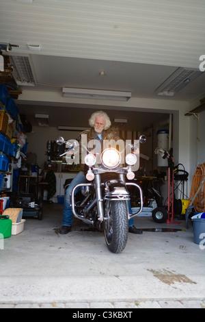 Mann auf Oldtimer Motorrad in der garage - Stockfoto