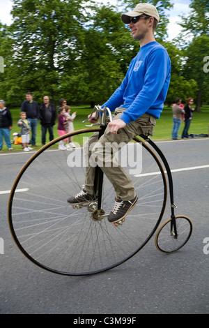 Mann mit dem restaurierten / überholten Hochrad Fahrrad auf einer Straße / Straße. - Stockfoto