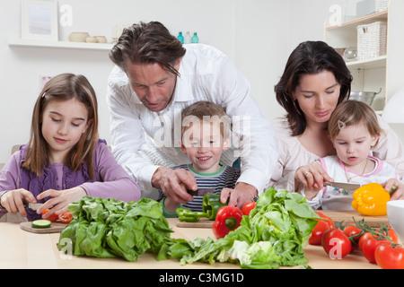Deutschland, Bayern, München, Mutter und Vater helfen, Kinder zu Salat vorbereiten - Stockfoto