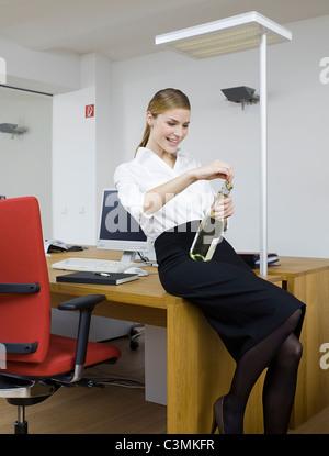 Deutschland, Köln, junge Frau genießen Sekt im Büro - Stockfoto