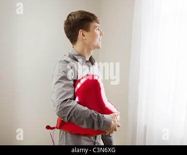 Mann hält herzförmige Ballons - Stockfoto