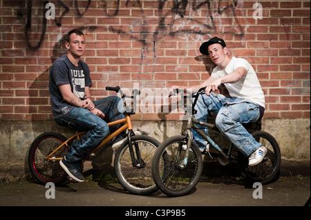 Zwei jungen im Teenageralter mit Einstellung auf BMX Stunt Bikes gelehnt eine Mauer, UK - Stockfoto