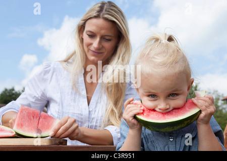 Deutschland, München, Mutter schneiden Wassermelone Slice für ihre Tochter (2-3 Jahre) - Stockfoto
