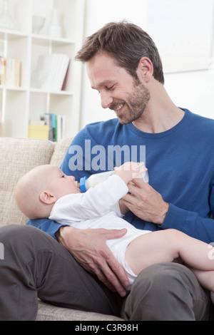 Deutschland, Bayern, München, Vater Fütterung Milch jungen (6-11 Monate) im Wohnzimmer - Stockfoto