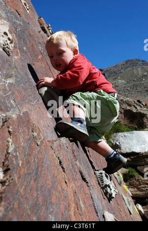 Ein kleiner Junge mit seinen ersten Eindruck von Klettern auf einer Outdoor-Wand in der Schweiz. - Stockfoto