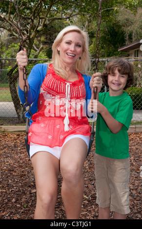 Blonde Mutter ein Dson spielen auf Schaukel Spielplatz - Stockfoto