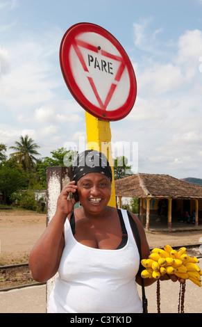 Lokale Frau am Handy im kleinen Dorf von Trinidad Kuba mit Stop-Schild Pare - Stockfoto