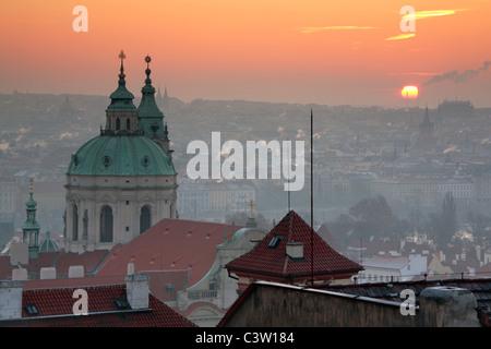 Sonnenaufgang über Prag mit der reich verzierten Kuppel der Kathedrale St. Nikolaus auf der Kleinseite - Stockfoto