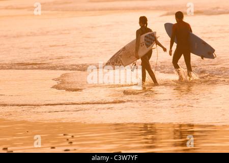Zwei Surfer entlang im flachen Wasser bei Sonnenuntergang - Stockfoto