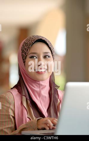 Junge hübsche asiatische muslimische Frau lächelt während der Eingabe von Notizen auf Laptop im café Stockfoto