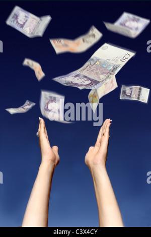 £10 und £20 Noten vom Himmel fallen, erreichen eine Frauenhand bis um zu fangen das Geld - Stockfoto