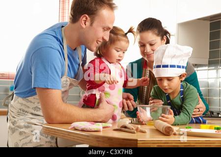 Junge Familie, gemeinsames Kochen in der Küche - Stockfoto