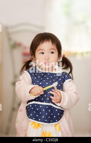 Baby Girl Holding Löffel - Stockfoto
