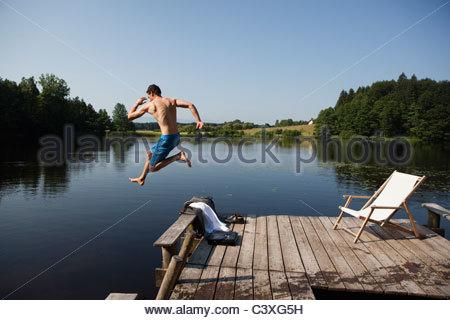 Junger Mann springt im See vom pier - Stockfoto