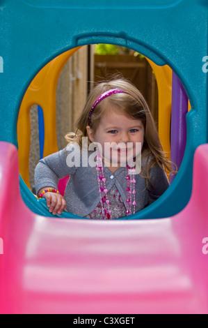 Vertikale Porträt eine niedliche kleine Mädchen Spaß spielen auf einer bunten Folie. - Stockfoto