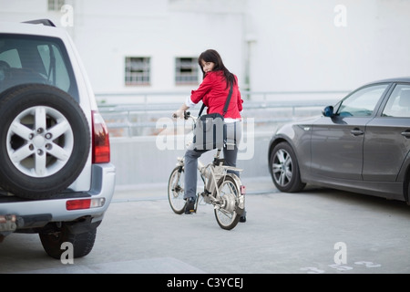 Frau, die ihr Fahrrad Parken - Stockfoto