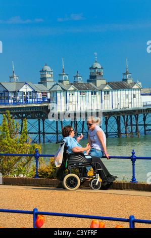 Ältere Frau in einem Rollstuhl im Chat mit einer jüngeren Frau auf Eastbourne Strandpromenade, East Sussex, UK - Stockfoto