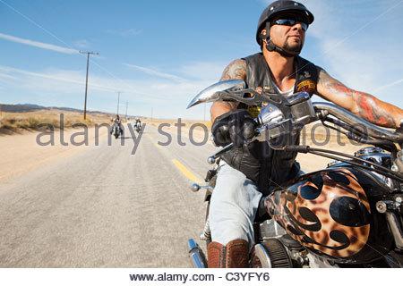 Drei Männer, die Motorradfahren entlang der Wüstenstraße - Stockfoto