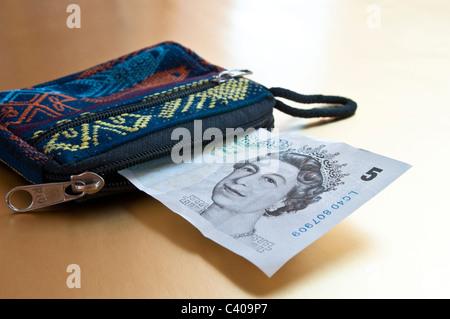 Fünf-Pfund-Note ragte aus der Handtasche - Stockfoto