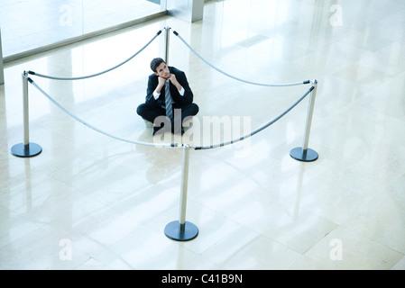 Geschäftsmann, sitzen am Boden im Inneren abgesperrt Bereich in der lobby - Stockfoto