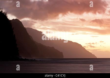 Nā Pali-Küste Wellen nach Sonnenuntergang. Das Meer ist ruhig und die Wolken verwischt durch eine lange Belichtungszeit - Stockfoto