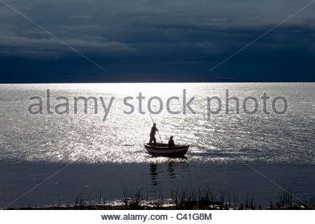 Zwei Jungs in einem kleinen Boot am Titicaca-See, von der untergehenden Sonne mit dunklen Gewitterwolken in der - Stockfoto