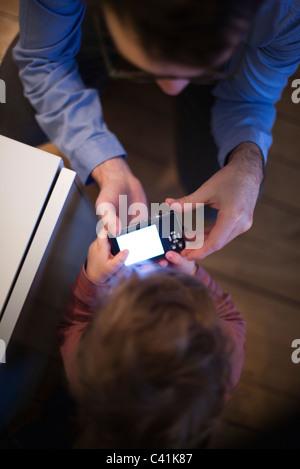 Vater und seinem kleinen Sohn Digitalkamera zusammen betrachten, Draufsicht - Stockfoto