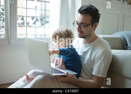 Vater und seinem kleinen Sohn Blick auf Laptop-Computer zusammen - Stockfoto