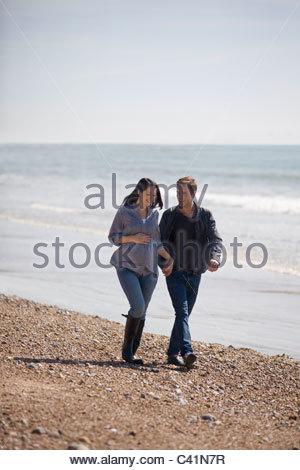Eine schwangere Frau und ihr Partner zu Fuß am Strand - Stockfoto
