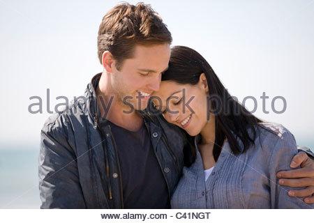 Porträt eines jungen Paares umarmen am Strand - Stockfoto