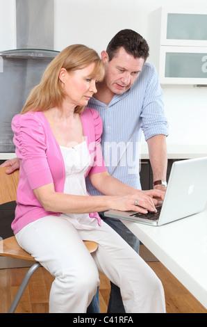 Paar auf der Suche am Laptop in Küche, besorgt oder ernsthafte Ausdrücke - Stockfoto