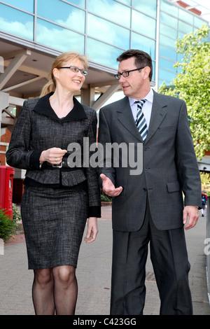 Mann und Frau in Anzügen zu Fuß entlang geht. - Stockfoto