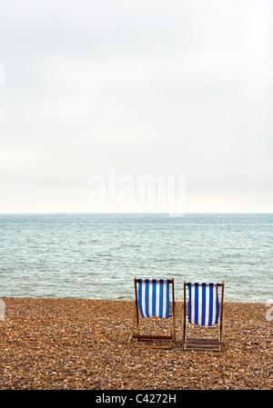 Zwei leere Liegestühle am Strand von Brighton.  Foto von Gordon Scammell - Stockfoto