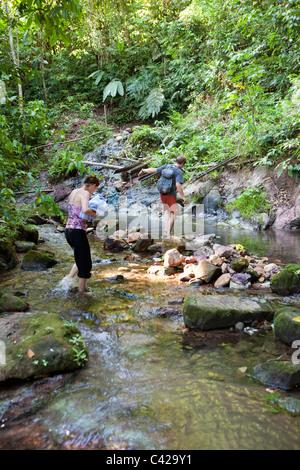Peru, Cruz de Mayo, Manu Nationalpark, UNESCO-Weltkulturerbe, Fredy Berge. Touristen, paar Kreuzung Stream. - Stockfoto