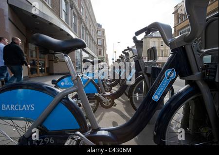 Eine Reihe von Barclays gesponsert Fahrräder Line-up auf dem Bürgersteig einer Straße in Basyswater, London. (Nur - Stockfoto