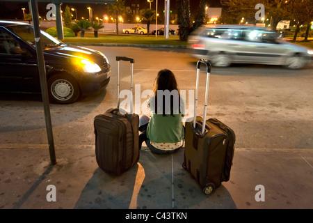 Frau mit Koffer warten auf Transport - Stockfoto