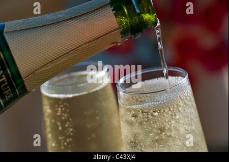 Champagner gießen gekühlte Gläser mit Blasen Champagner auf sonnenbeschienenen Terrasse mit bunten Bougainvillea - Stockfoto