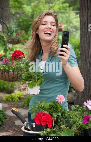 Hübsche junge Frau, die Pflanzen der Blumen in ihrem Garten auf Handy - Stockfoto