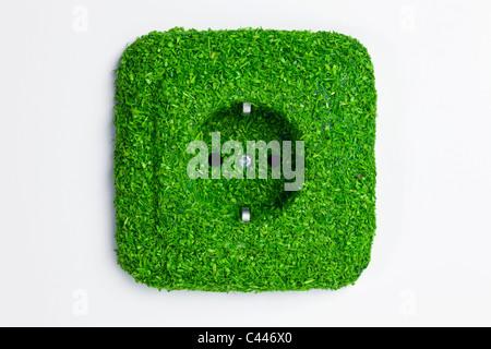 Energiesparende elektrische Steckdose in grünen Rasen bedeckt - Stockfoto