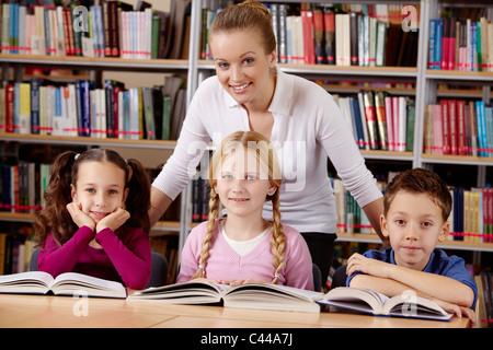 Porträt von Schülern und Lehrer Blick in die Kamera mit einem Lächeln in Bibliothek