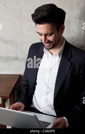 Ein Lächeln auf den Lippen Geschäftsmann arbeiten auf einem Laptop, erhöhte Ansicht - Stockfoto
